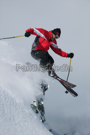 skier jumping of a rock