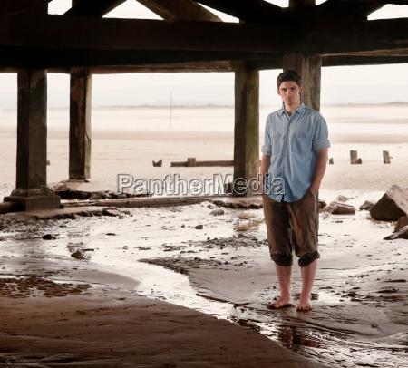 man standing by stream on beach