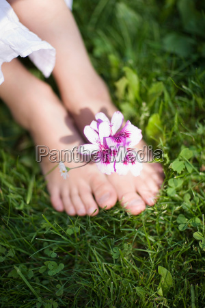 childrens feet with a flower