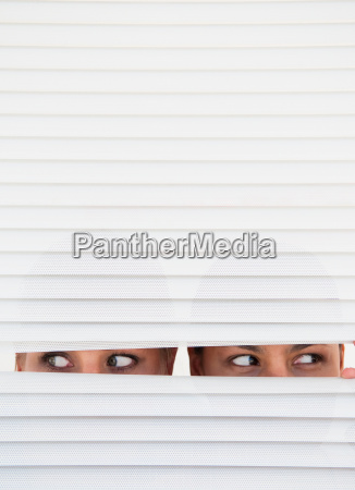 two women look through blinds