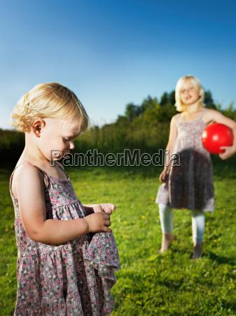 sad toddler girl playing with sister