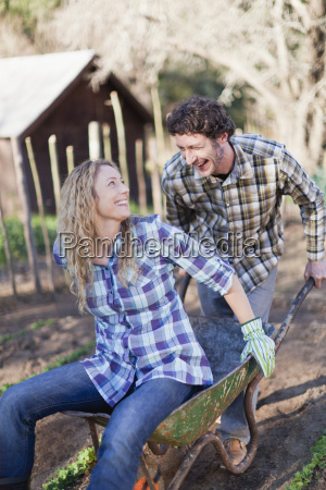 man pushing girlfriend in wheelbarrow
