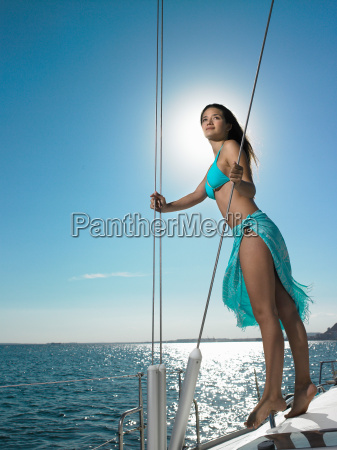 young woman standing on yacht at