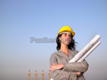 woman in hard hat holding drafts
