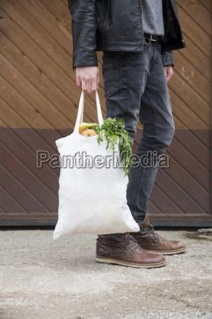 adolescente ragazzo portando borse riutilizzabili pieno