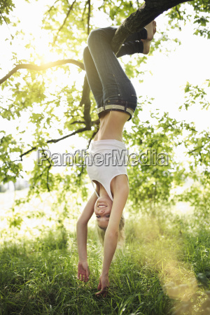 young woman hanging upside down from