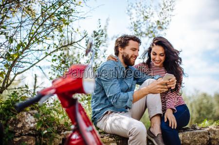 giovane coppia seduto sul muro in