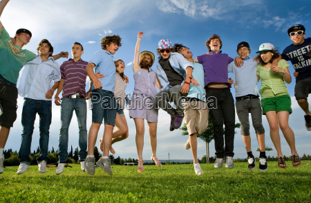 teen group jumping in park