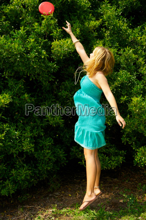 woman jumping to reach a frisbee