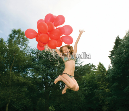 girl with red balloons jumping in
