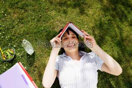 woman shielding face with book