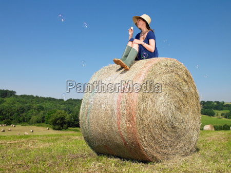 girl on bale of hay blowing