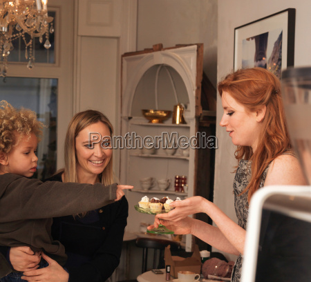 woman offering cakes to young boy