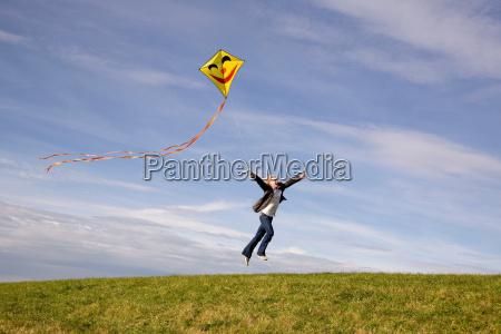 man jumping flying a kite