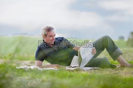man sitting on grass reading newspaper