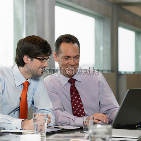 two businessmen looking on laptop