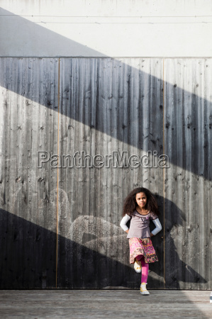 young girl leaning on wall