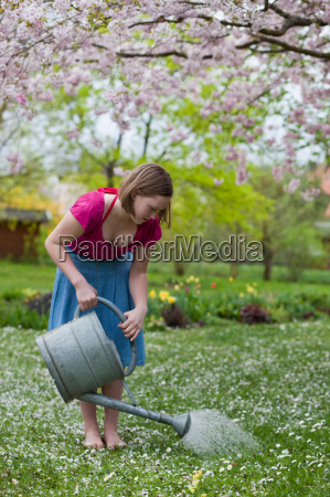 young girl watering grass