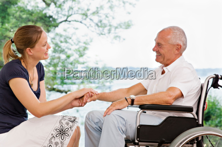 woman holding senior mans hand