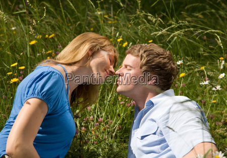 man woman kissing in grass with
