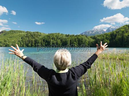 senior woman standing by lake rear