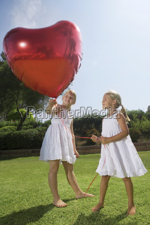 young girls holding red heart balloon