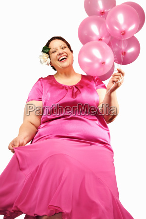 large woman holding bunch of balloons
