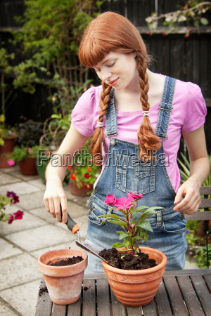 woman repotting plant in garden