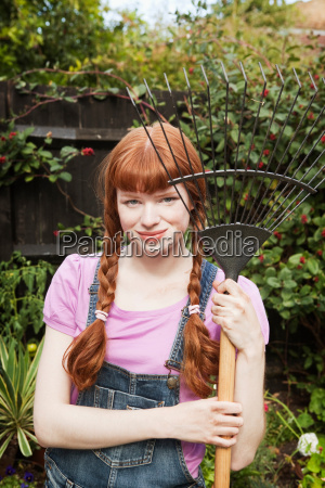 woman holding grass rake in garden