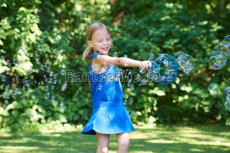 girl playing with bubbles in backyard