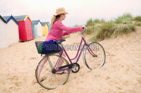 women pushes bicycle over beach