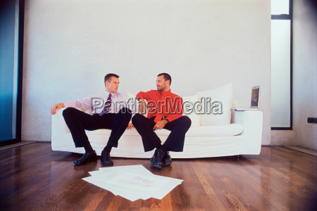 businessmen talking on couch in office