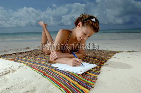 woman writing on beach