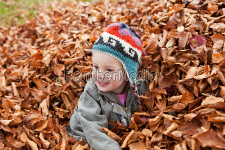 girl playing in pile of leaves