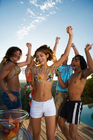 young people dancing on terrace by