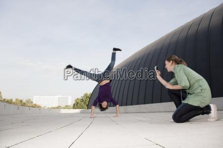 teenage girl photographing young man doing