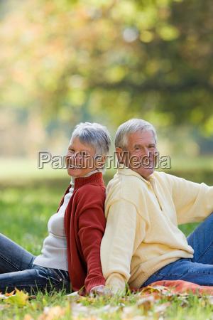 senior couple sitting back to back