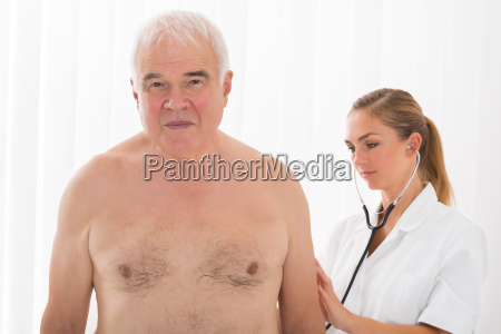doctor examining patients back with stethoscope