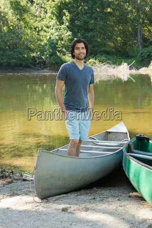 young man standing in rowboat