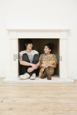 young couple sitting in a fireplace