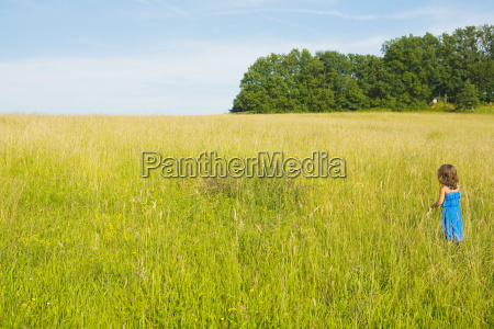 a girl standing in a field