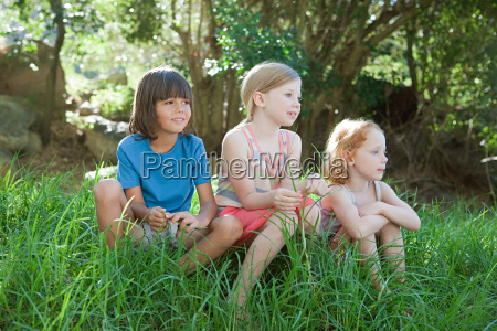 three children sitting on grass