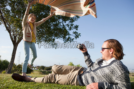 young man photographing girlfriend as she