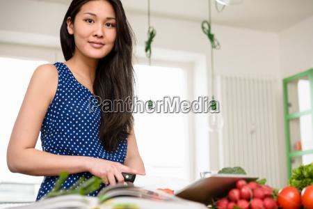 woman slicing tomatoes looking at camera