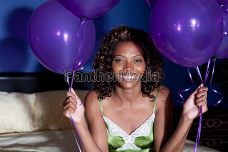 young woman on bed holding balloons