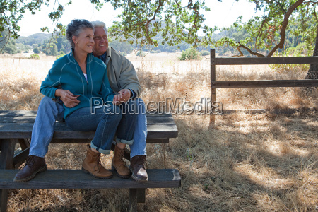 mature couple sitting on picnic table