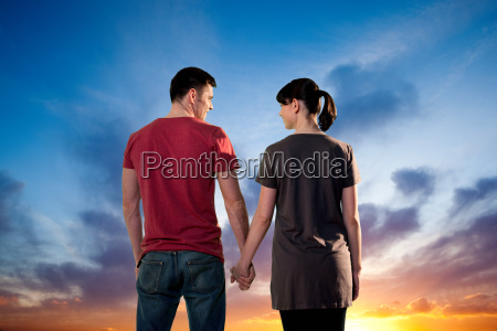 couple holding hands against dramatic sunset