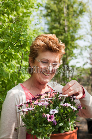woman looking at pot plant in