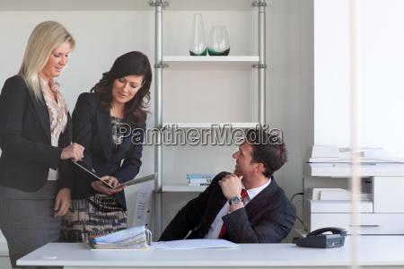 businesswomen talking to businessman at desk