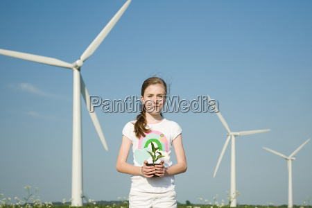 girl with plant by wind turbines